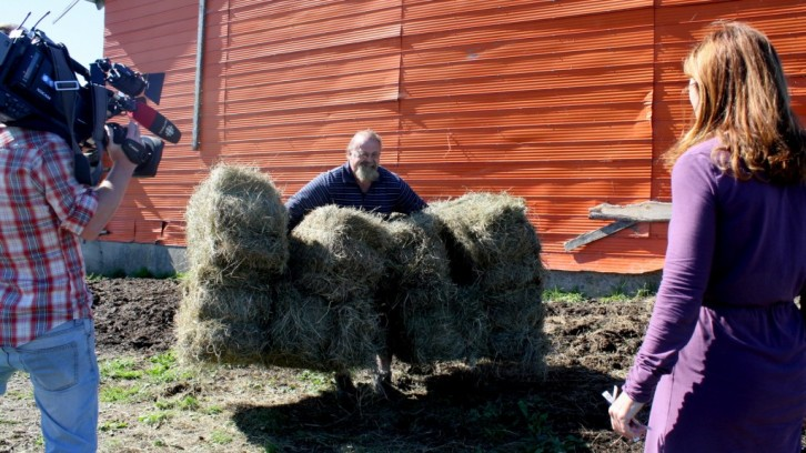 Colleen Jones and her cameraman watch a strongman lift eight hay bales at once.