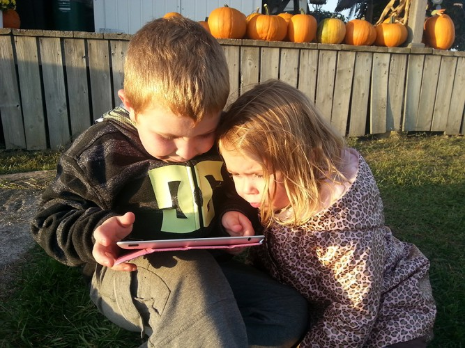 Today's kids set aside toys for the glow of a screen. Joel Lewis, 6, uses an iPad to surf the net while younger sister Hilary, 4, looks on.