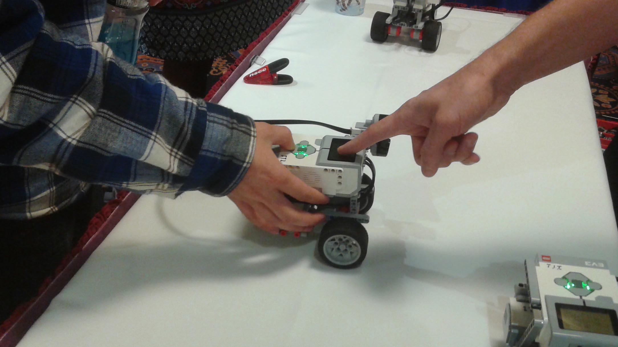 A Nova Scotia Community College recruit shows a student how to use a Lego robot.