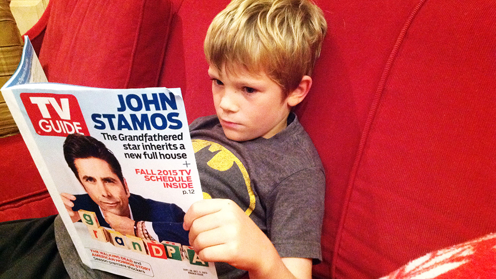 Vaughan, 6, flips through the TV guide for programmes of interest to him.