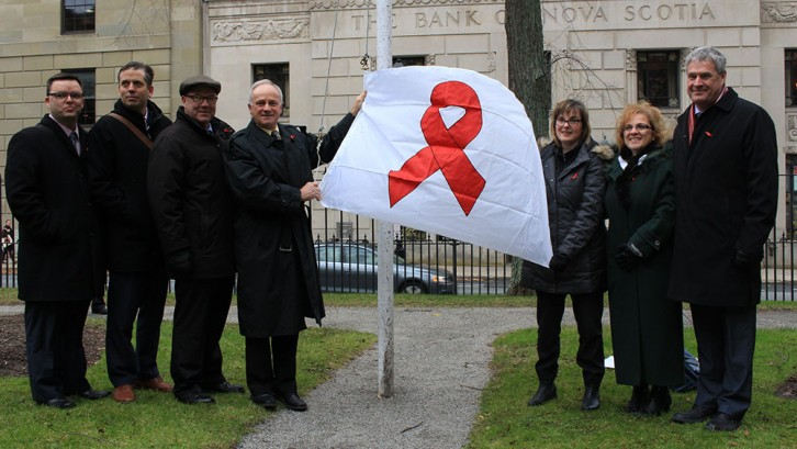 Health Minister Leo Glavine raisies a red ribbon flag for AIDS Awareness Week