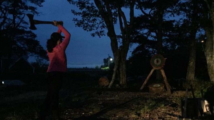 Erin Smith throws an axe at a target. The club turns on a car's headlights to be able to keep throwing in the dark.