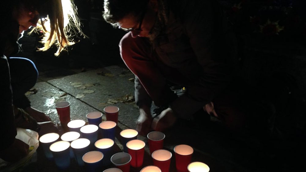 Attendees light candles to remember those lost in the Paris attacks.