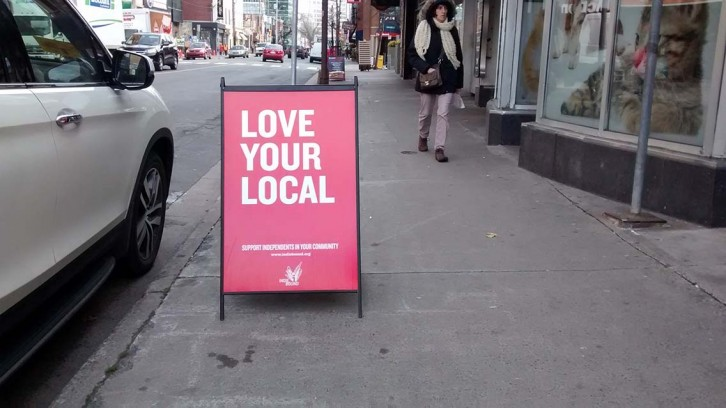 A sign outside Bookmark bookstore on Spring Garden Road encourages shoppers to buy local
