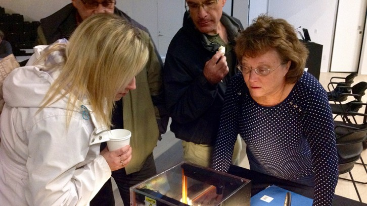 Guests at the science talk in Paul O'Regan Hall watch as a glass box fills with radon gas.