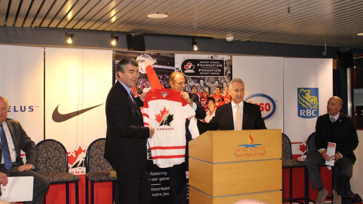 Jim Treliving & CEO of Hockey Canada, Tom Renney, present Premier McNeil with Hockey Canada jersey