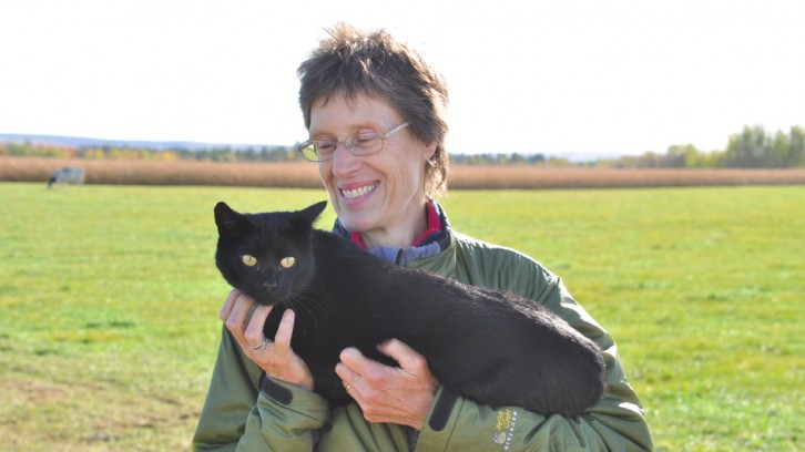 Irma Langelaan cuddles with a barn cat on her dairy farm in Aylesford, N.S.