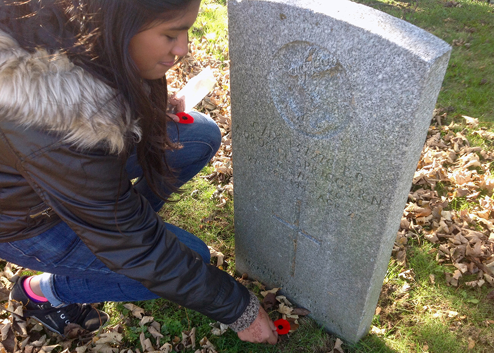 Grade nine students pay tribute to Canada's fallen soldiers by placing a poppy at the foot of each headstone.