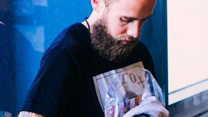 Nathan Slavik is the managing editor at DJBooth. He is seen looking on at his phone.