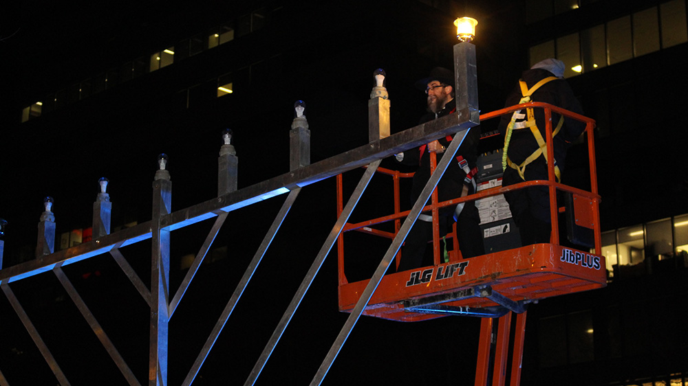 Rabbi Mendel Feldman lights a large menorah in Grand Parade Square on Monday evening.