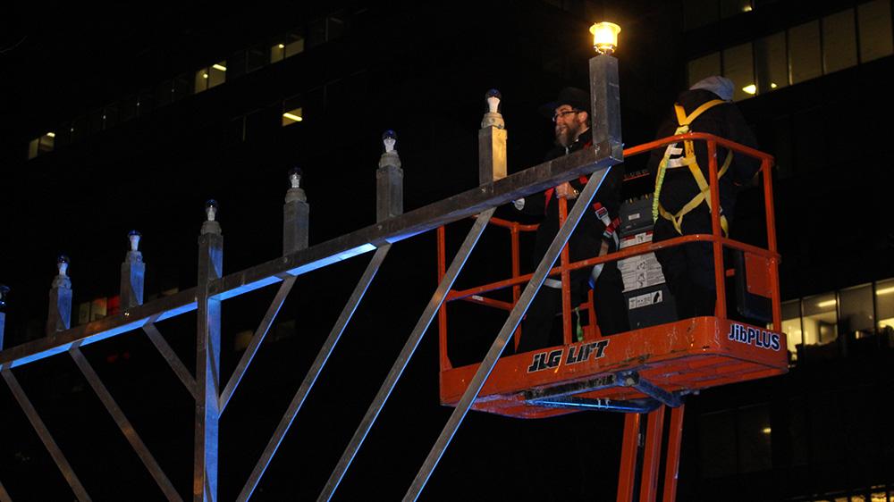 Rabbi Mendel Feldman lights a large menorah in Grand Parade Square on Monday evening.