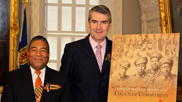 Minister of African Nova Scotian Affairs Tony Ince and Premier Stephen McNeil stand with the official poster for African Heritage Month 2016.