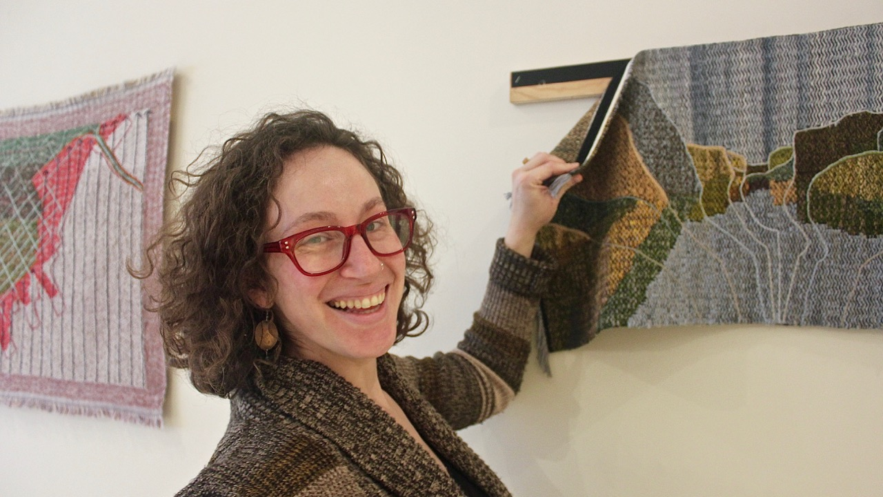 Textile artist Rilla Marshall peels a handwoven map from its mount at the Mary E. Black Gallery downtown.