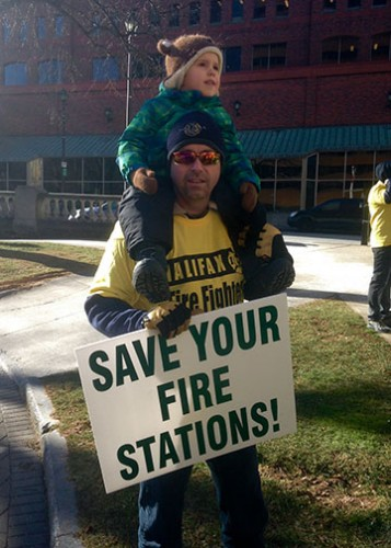 Brad Simms, a firefighter from Station 2 on University Avenue, and his son Benjamin protested outside City Hall.