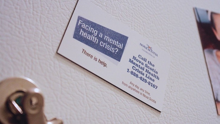A fridge magnet with the phone number to the province's mental health crisis line.