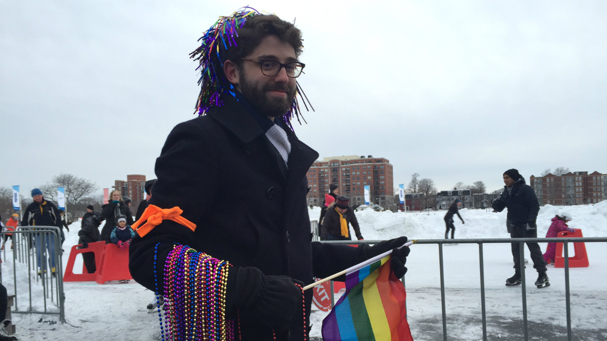 Jason, a volunteer with Halifax Pride, passed necklaces and rainbow banners to skaters who wanted to join the event.