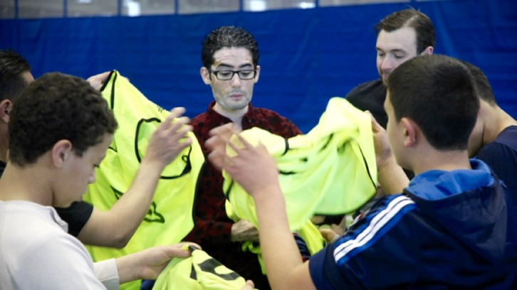 An Arabic speaking volunteer hands out jerseys before the start of the game.