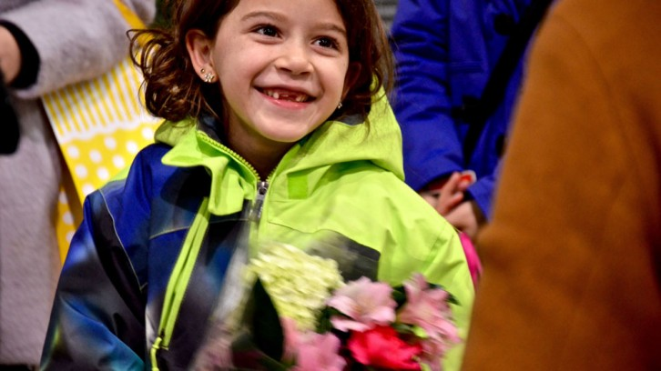 One of the children smiles at the flowers her family was given.