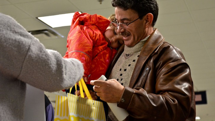 Sponsors hand a gift bag to a refugee family at the Halifax airport