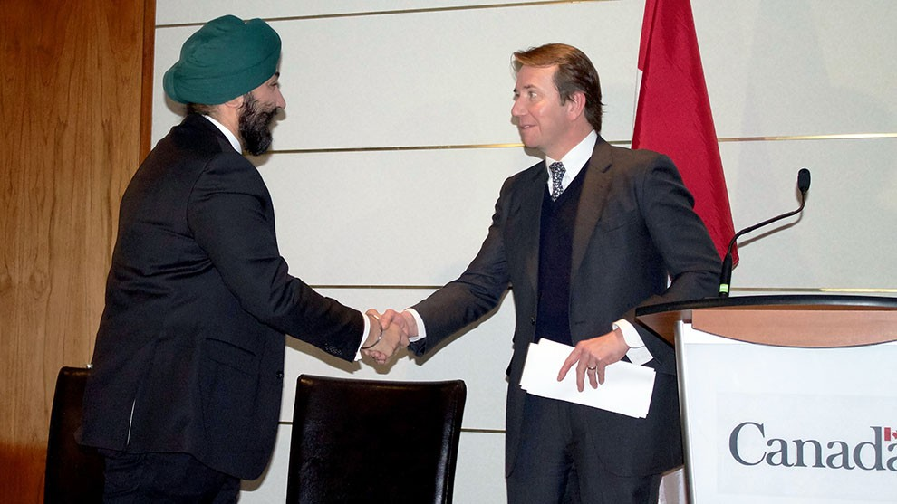 Economic Development minister Bains shakes hands with Treasury Board president Scott Brison before announcing the new investments.