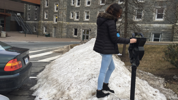 A student puts money in a meter at Saint Mary's University