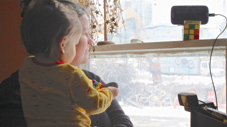 A mother and child look out their living room window at a construction site.