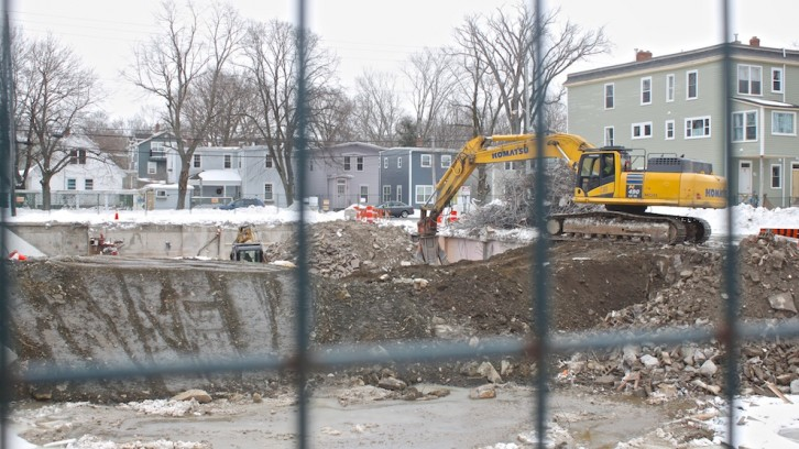 A backhoe excavates a pit on Quinpool Road.