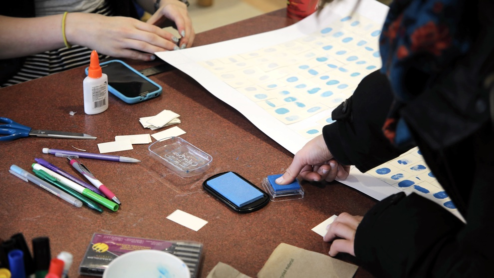Students add their own fingerprint to the mural to represent unique recoveries in mental health