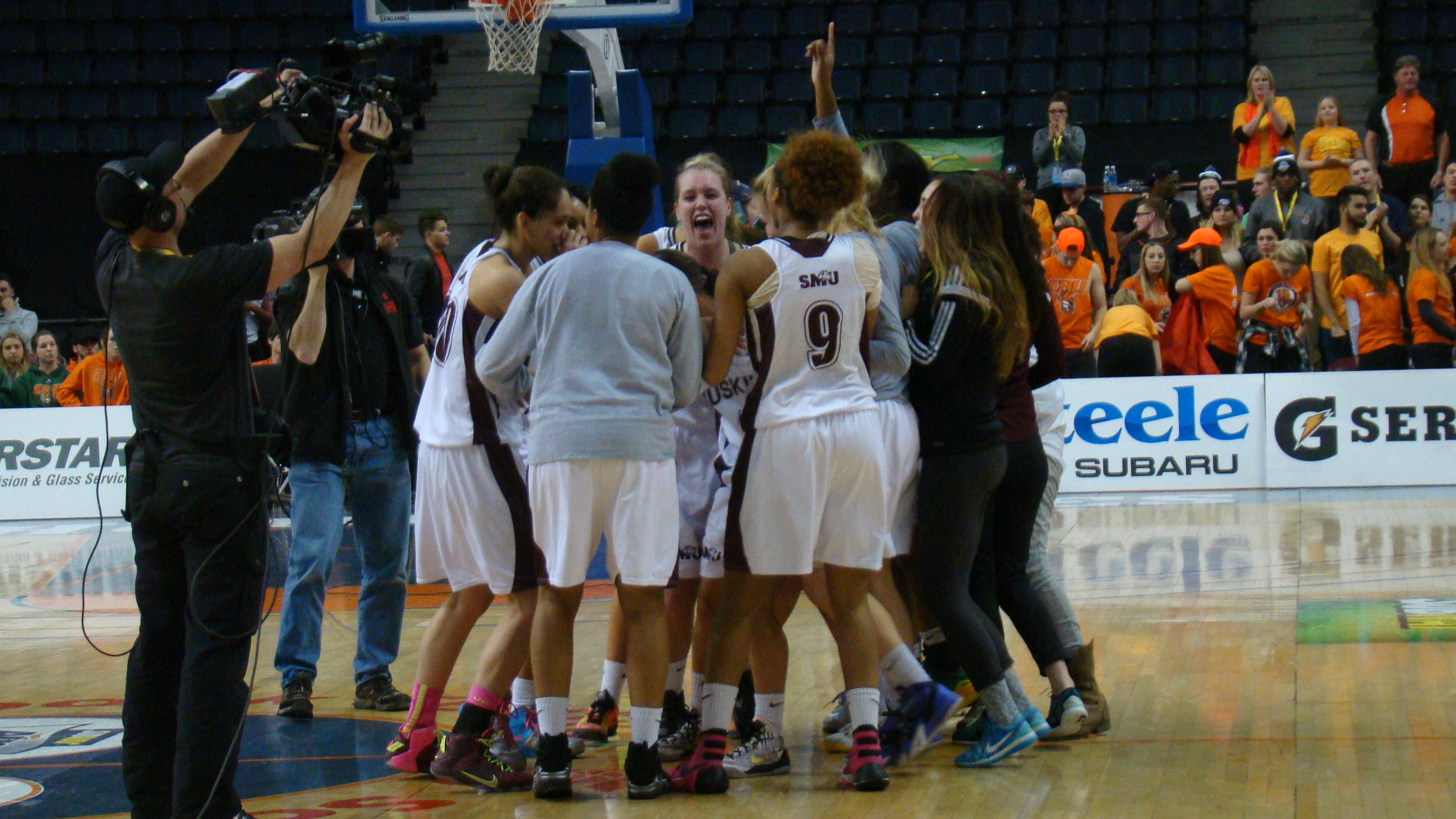 SMU Huskies celebrate their victory as Queen's We are the Champions fills the gym