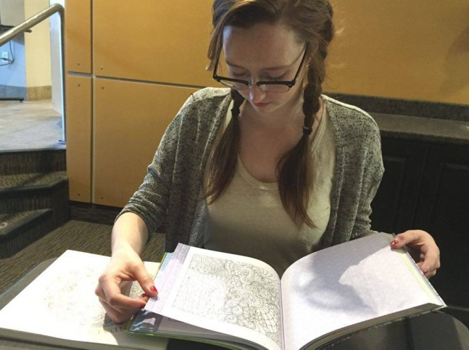 Katie Brousseau going through her adult colouring book.