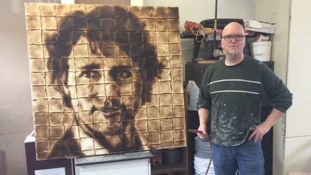 Chris Joyce holds his blow torch next to his portrait of Justin Trudeau