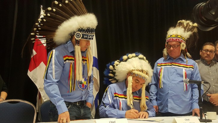 Glooscap First Nation Chief Sidney Peters (middle) signs the registry.