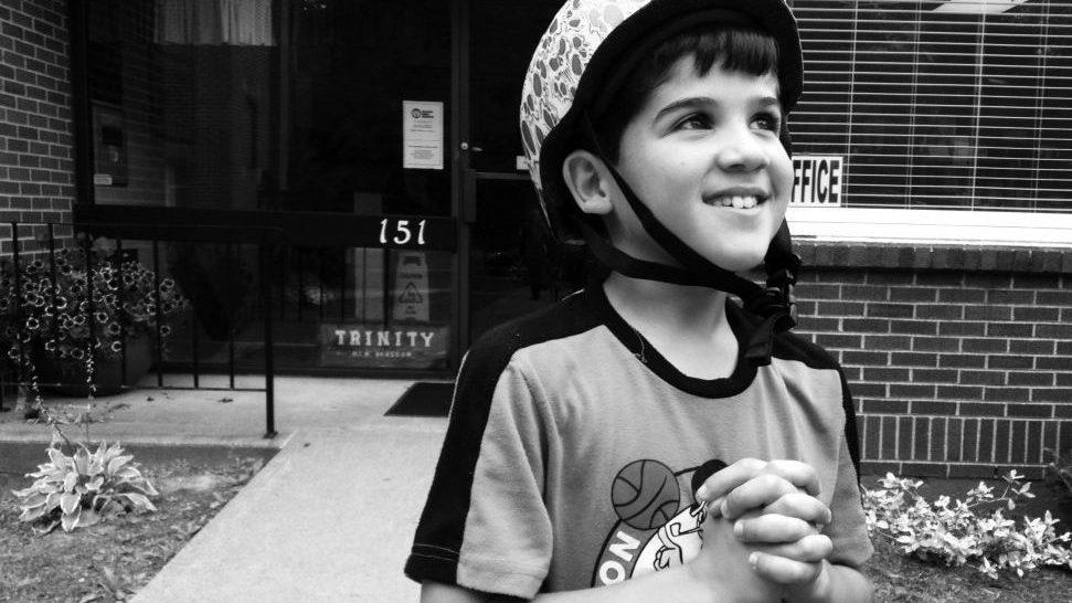 Abdullah AlMethyb, 8, takes a break from riding his bike around Trinity United Church in New Glasgow, NS.