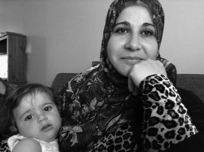 Rania AlMethyb holds her youngest daughter, Raneem, at their home in New Glasgow.