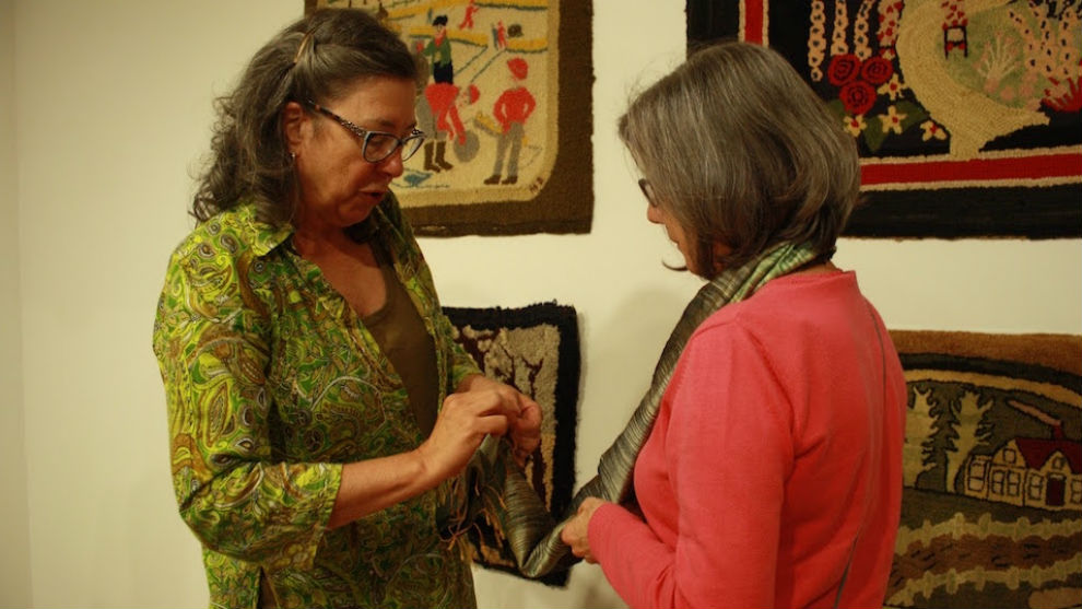 Liza Hageraats, left, explains a rug hooking technique to Carolyn Harry