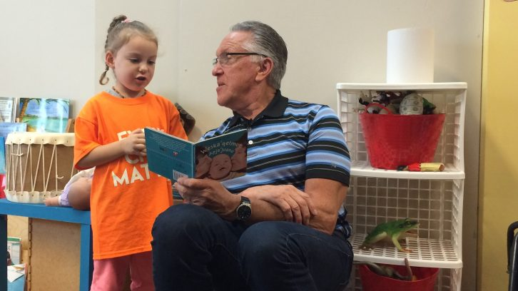 Bernie Francis reads in Mi'kmaq to four-year old Brielle Pennell.