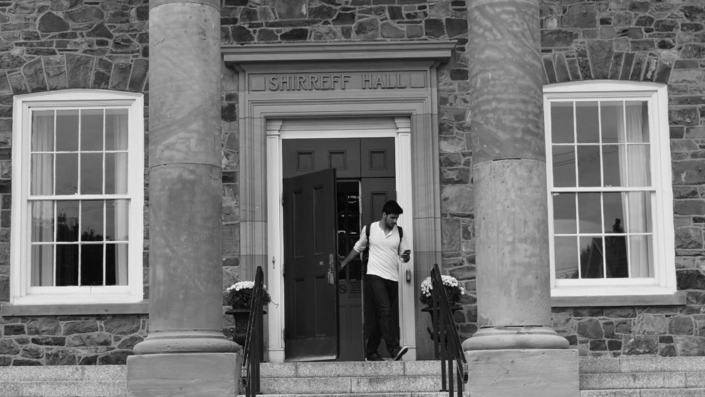 A student leaves out the front door of Shirreff Hall.