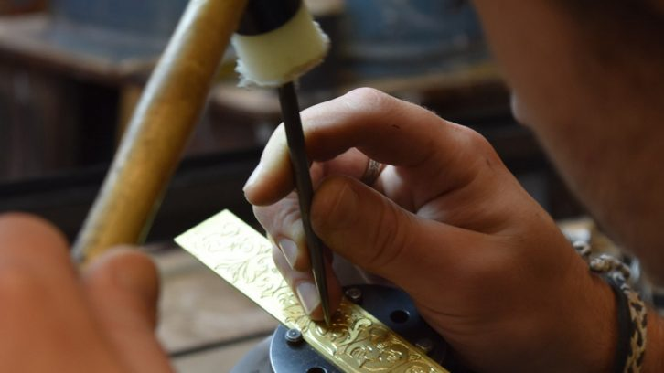 Nicholas Rosin engraves a bracelet with a hammer and chisel.