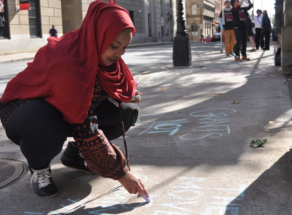 Amina Abawajy uses sidewalk chalk to demand accessible post-secondary tuition for students in Nova Scotia.