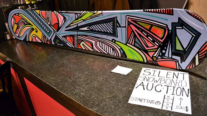 A used snowboard painted by Andrew MacKeen for the silent auction at the Broken Deck Art Show.