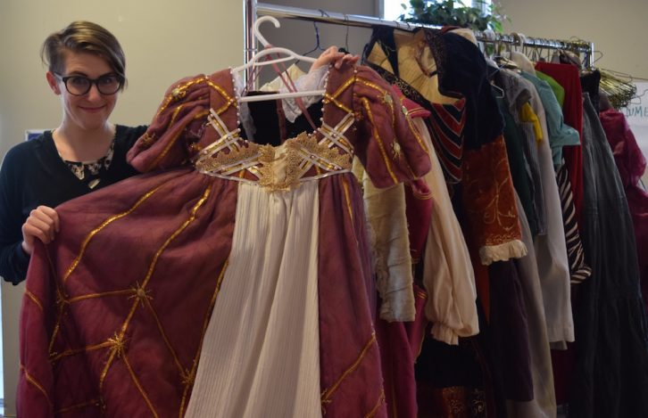 Colleen MacIsaac, artistic producer of the Villain's Theatre, holds a costume up for sale, which was originally used for a production of The Duchess of Malfi.