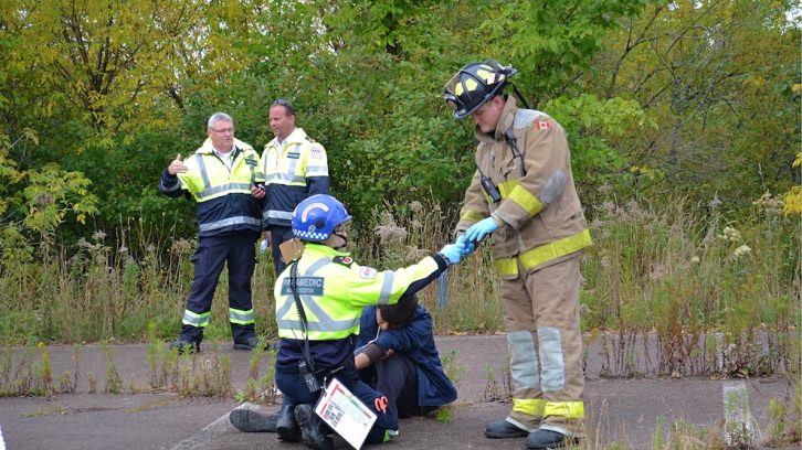 A paramedic passes a firefighter coloured bands for triage, determining seriousness of injury.