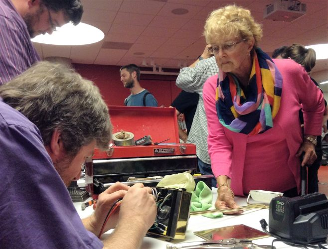 Peter Spierenburg with Halifax Maker Space helps Rose Marie Mahr fix her lamp. Halifax Maker Space is a group that repurposes materials in various ways.
