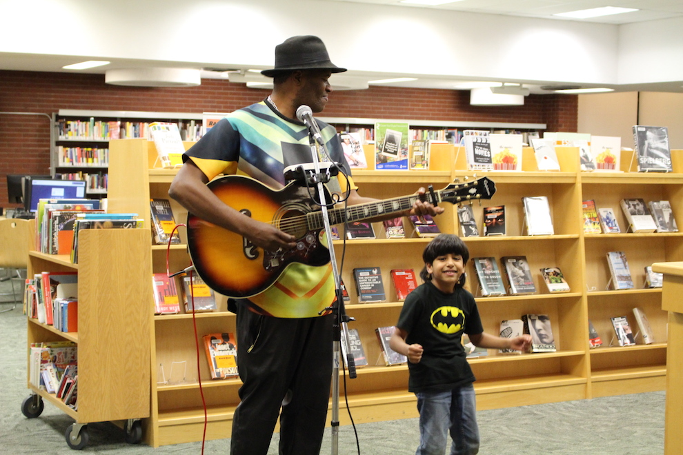 Musician Dammien Alexander (left), plays for guests. Jawad Albarakati (right) dances to his songs.