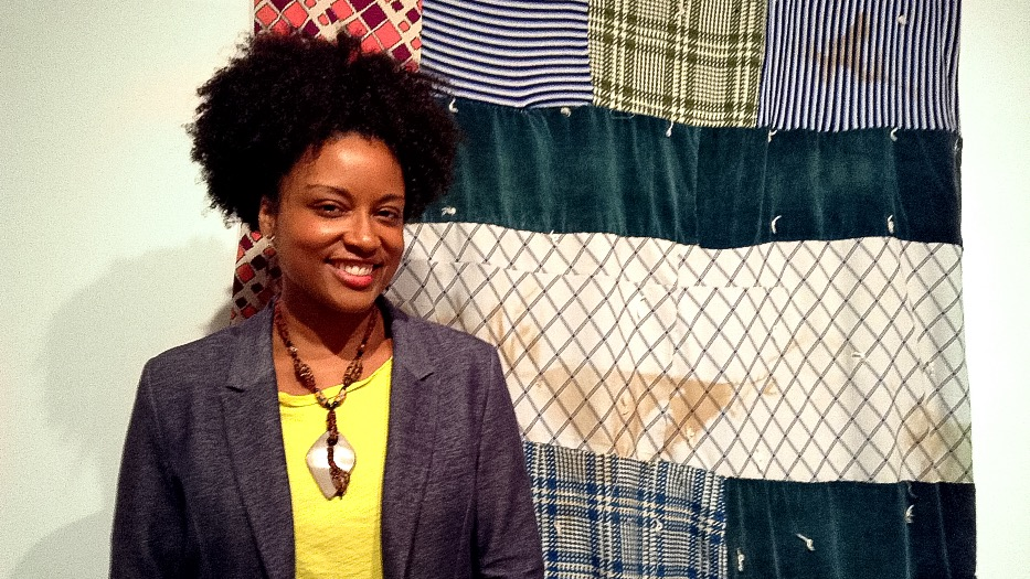 Shauntay Grant in front of her favourite quilt. This quilt shows the burn marks from one of the house fires it survived.
