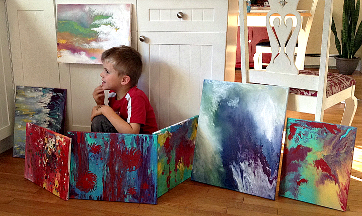 Lukas surrounding himself with a handful of his paintings.