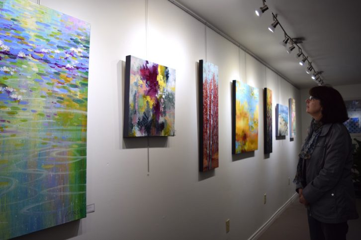 Louise Baker's art collection includes a mixture of scenic and abstract paintings.