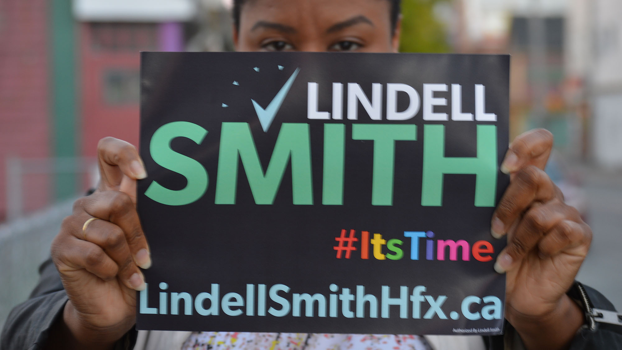 LaMeia Reddick, a volunteer in Lindell Smith's campaign holds up one of his many campaign signs.