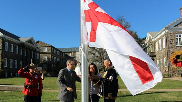 Dalhousie President Richard Florizone (L), Dalhousie science student Melanie Hardie (centre) and Grand Keptin Andrew Denny of the Mi'kmaq Grand Council raise the Grand Council Flag together