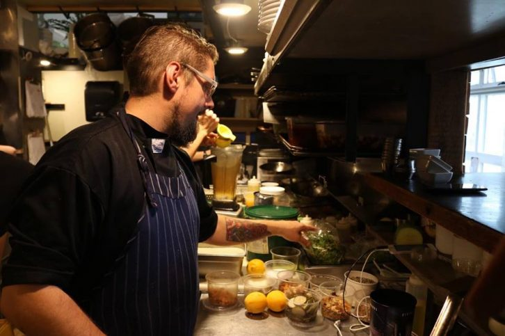 EnVie chief Todd Bright prepares food for dinner service.